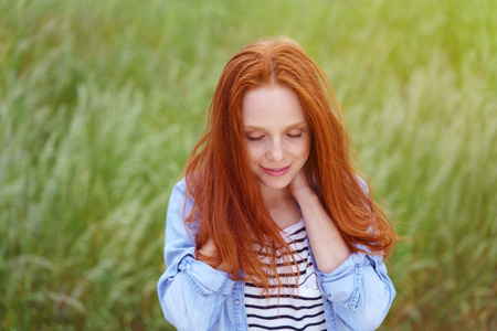 Young attractive woman with long red hair relaxing in a grassy field with her hands clasped behind her neck and eyes closed