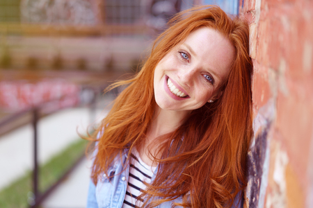 redhaired: Pretty redhead woman with a lovely friendly smile leaning against a brick wall in an urban environment beaming at the camera, close up head and shoulders