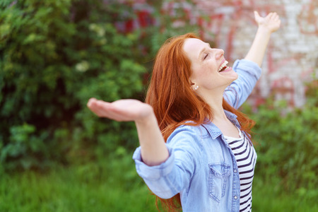 outspread: Laughing young redhead woman rejoicing in spring standing with closed eyes and her arms outspread in a lush green spring garden