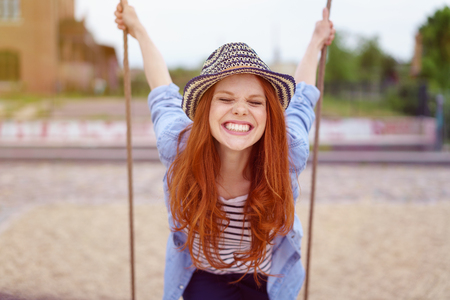 rolled up sleeves: Overjoyed single red haired young woman in hat and blue denim shirt with rolled up sleeves sitting on swing at urban playground