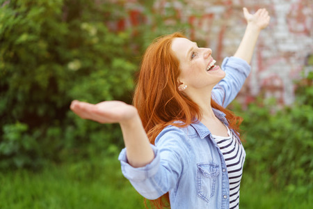 outspread: Happy young woman celebrating the spring standing outdoors in a lush green garden with outspread arms and a beaming smile