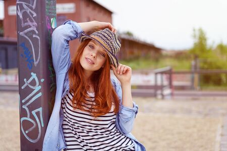 seductive look: Trendy pretty young redhead young woman in a seductive pose leaning against a graffiti covered pole outdoors giving the camera a sultry look Stock Photo