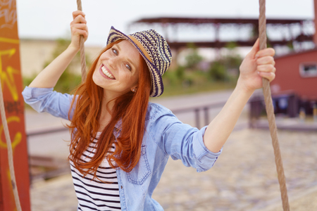 Cute young redhead woman in a trendy hat holding the ropes on a swing in an urban playground grinning at the camera