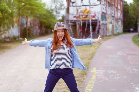 extrovert: Extrovert trendy young redhead woman posing with outstretched arms on a rural road yelling at the camera
