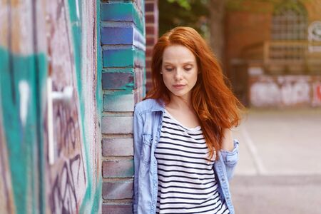 Thoughtful young redhead woman with downcast eyes standing outdoors leaning against a graffiti covered brisk wall looking down with a serious expression Stock Photo