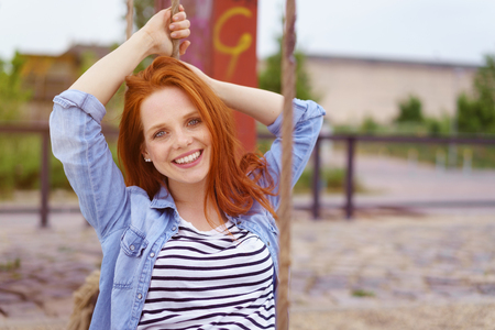 rolled up sleeves: Happy single red haired young woman in blue denim shirt with rolled up sleeves sitting on swing with thick ropes at urban playground