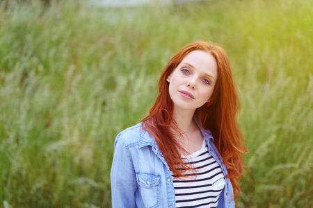 head tilted: Lovely young redhead woman in a grassy field standing with her head tilted looking quizzically at the camera, upper body with copy space Stock Photo