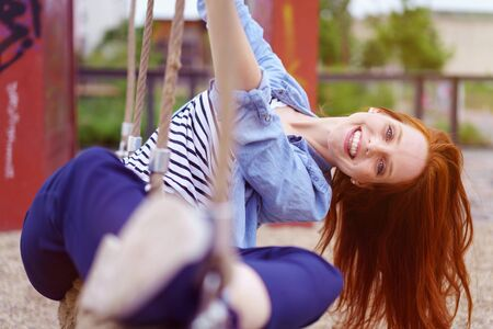 woman rope: Carefree young woman playing on a rope swing leaning to the side laughing at the camera outdoors in a playground Stock Photo
