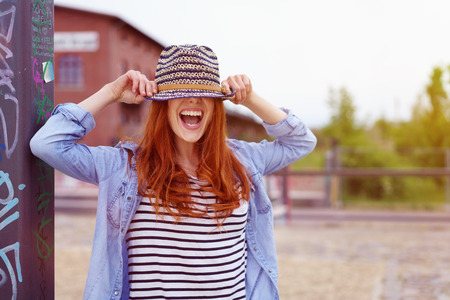 pulled over: Laughing playful woman hiding under a trendy straw hat that she has pulled down over her eyes as she stands in an urban park outdoors Stock Photo