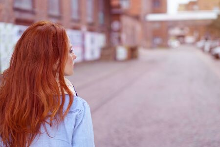 Young woman with gorgeous long red hair walking away from the camera along a deserted urban street, with copy space Foto de archivo