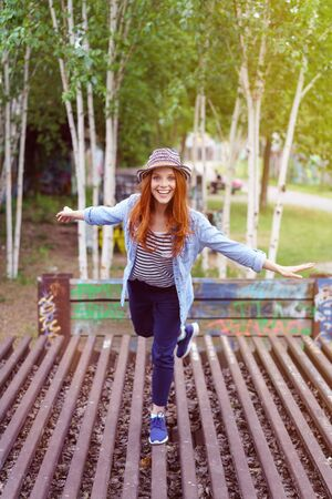 playful: Playful vivacious young redhead woman balancing on a wooden slatted deck on one leg laughing at the camera