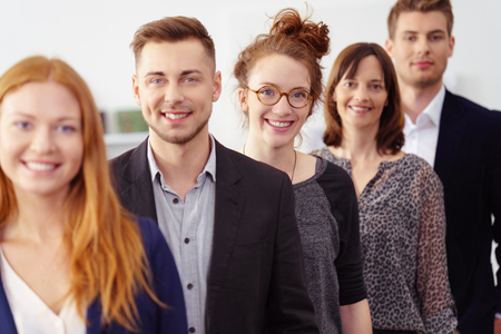Smiling group of young professionals in office wearing business attire while standing in a line Stockfoto