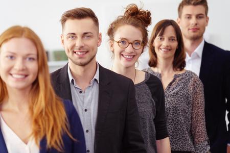 grupo de jóvenes profesionales en la oficina usando traje de negocios sonriendo mientras está de pie en una línea Foto de archivo