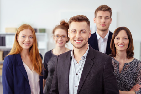 Small group of coworkers in business attire stand closely and smile at the camera