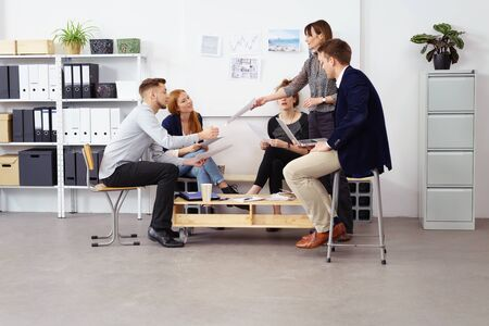 work area: Female supervisor passing around agenda schedules to employees during meeting at small office with storage shelves and white bulletin board in background Stock Photo