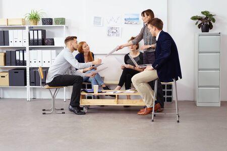 reunion de trabajo: supervisora ??que pasa alrededor de los horarios del programa a los empleados durante la reunión en una oficina pequeña con estantes de almacenamiento y tablón de anuncios en el fondo blanco