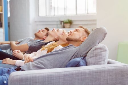 lean back: Four young friends lean back and look upwards while seated in a row on a grey couch in living room