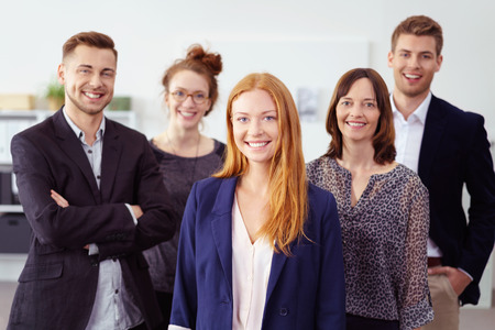 business casual: Smiling young adult woman in red hair and blue blazer jacket standing in front of cheerful people in business casual attire