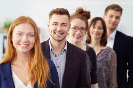 attire: Smiling group of young professionals stand in line wearing business attire and lead by beautiful woman with red hair Stock Photo