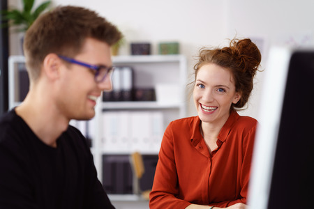 Male and female business partners smile at camera while working on computer in bright room near short shelves