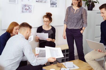 small group: Smiling female supervisor standing over small group of employees reviewing paperwork during meeting with white bulletin board in background