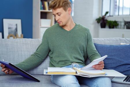 viewing: Young man studying or working from home sitting on a sofa with a large binder of notes reading a document, close up three-quarter view