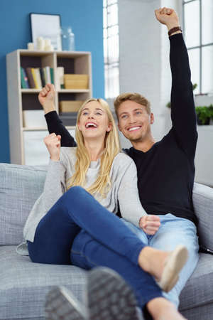 exultant: Happy exultant young couple sitting cheering and laughing on a sofa at home punching the air with their fists