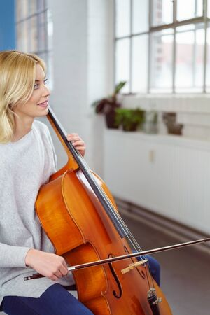 bow window: Smiling cellist holding her instrument and bow stares towards the window while seated in her living room