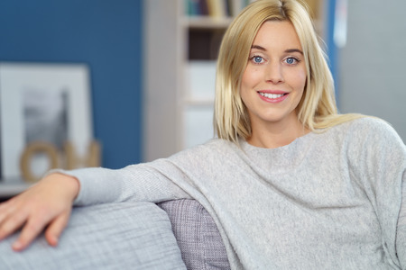 unwinding: Pretty young blond woman unwinding at home relaxing on a comfortable sofa looking at the camera with a friendly smile