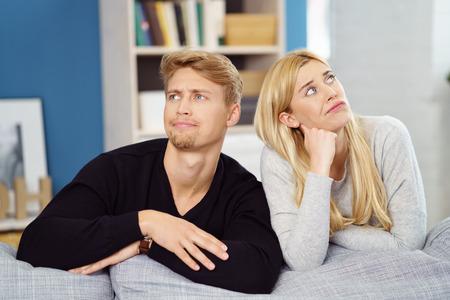 novios enojados: Imagen de la diversión de una pareja joven reflexiva apoyándose en el respaldo de un sofá juntos mirando hacia arriba en direcciones opuestas con expresiones pensativas peculiares Foto de archivo