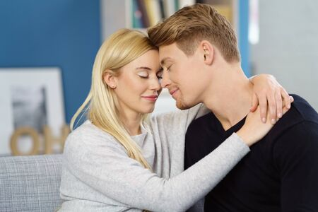 sentimental: Sentimental loving young couple sharing a tender moment with their eyes closed and foreheads touching and smiles of bliss Stock Photo