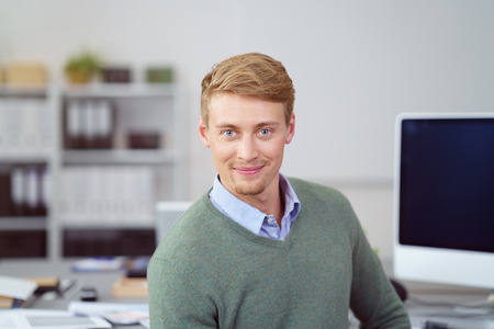 businessman working at his computer: Friendly young businessman smiling at the camera as he turns in his chair at the office while working at a desktop computer