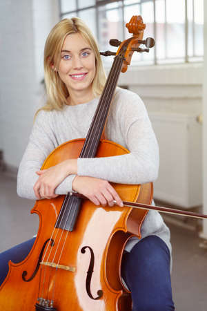 cellist: Blond cellist hugs her instrument and smiles at camera while holding bow in hand and seated in her living room