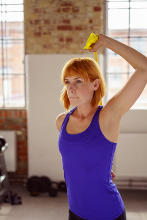 elastic band: Woman exercising in fitness studio by windows and hand weights stacked along the wall
