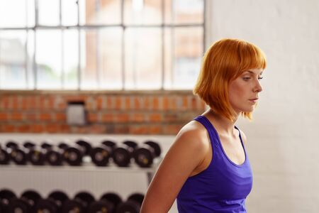preoccupied: Serious fit young redhead woman walking across a gym looking down with a preoccupied expression with gym equipment in the background