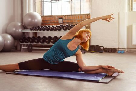 supple: Athletic supple young woman working out in a gym doing aerobic yoga exercises on a mat in a graceful pose