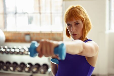 extends: Determined young woman working out with dumbbells as she extends her hand with a weight towards the camera, focus to her face