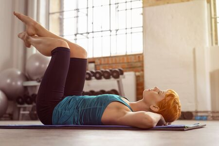 doing: Young woman working out doing leg raisers on a yoga mat in a gym with her eyes closed as she relaxes in this position