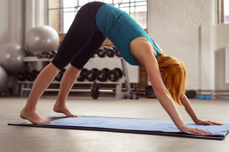 bending over: Supple toned woman working out in a gym bending over a mat with her hands on the ground and back arched in a health and fitness concept Stock Photo