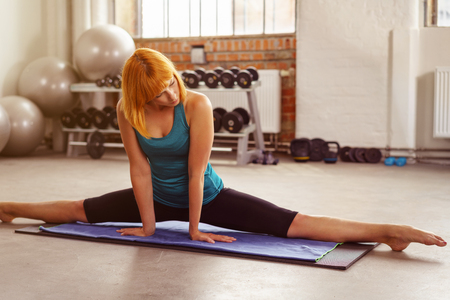 dance studio: Supple attractive fit young woman doing the splits on a mat in the gym to improve her mobility , close up view with gym equipment behind Stock Photo