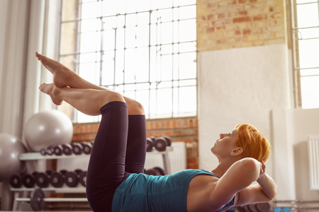 strengthen: Young woman doing sit ups to strengthen her abdominal muscles as she works out on a yoga mat in a gym, close up side low angle view Stock Photo