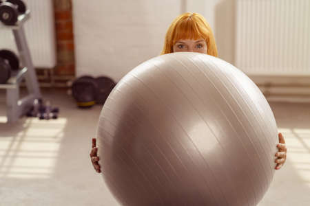 'hide out': Young woman holding a pilates ball in front of her in a gym with only her smiling eyes visible over the top