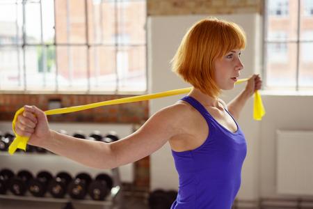 Mooie atletische vrouw met kort rood haar maakt gebruik van gele stretchband tijdens het trainen in een fitnesscentrum Stockfoto