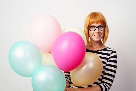 grins: Smiling happy woman wearing glasses holding a bunch of colorful festive party balloons as she grins at the camera, upper body over white