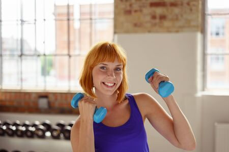 grins: Happy fit young woman working out in a gym with weights holding two dumbbells in her raised hands as she grins at the camera