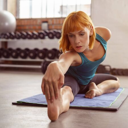 clasping: Supple young woman working out in a gym doing stretching exercises on a mat clasping her toes with a serious expression, facing towards the camera