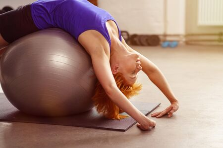 lying on back: Healthy active young woman doing pilates in a gym lying back over the ball with her hands on the floor, close up side view with copy space Stock Photo