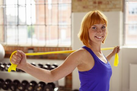 elastic: Red headed athlete holds yellow stretch band across her shoulders while exercising in a fitness center near hand weights Stock Photo