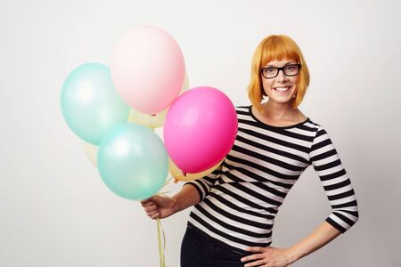 grins: Happy stylish woman wearing glasses and a striped top holding a bunch of colorful party balloons in her hand as she grins happily at the camera, isolated on white Stock Photo