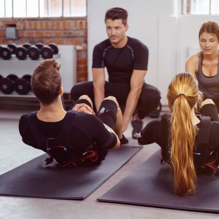 sit on studio: Male and female athletes perform sit ups on yoga mats in fitness studio as their instructors help them Stock Photo
